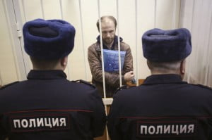 Photographer Denis Sinyakov of Russia stands in a defendants' cage during a court session in St. Petersburg on Nov. 18, 2013. REUTERS/Maxim Zmeyev