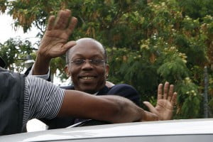 Former Haitian President Jean-Bertrand Aristide waves to supporters as he arrives in Port-au-Prince, May 8, 2013 to testify on the killing of journalist Jean Léopold Dominique. A new report alleges that a senator close to Aristide was the mastermind behind the killing. REUTERS/Marie Arago