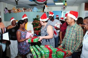 CEO of Standard Distributors, Katrina Newton (centre) and other Standard members spread the Christmas spirit with a gift for parent Alexis Roach and baby, McKenzie Haqq.