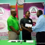 Left To Right: CEO Glendon Belle, Olympian Andrew Hinds & COB President Christopher Oliver presenting the cheque