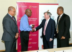 Project lead Dr. Wayne Charles-Soverall, expresses his gratitude to Chief Executive Officer, CIBC FirstCaribbean, Rik Parkhill, while Director of the Comtrust Board & Managing Director Retail & Business Banking, Mark St. Hill and Principal and Pro-Vice-Chancellor of the UWI Cave Hill Campus, Professor Sir Hilary Beckles, look on.