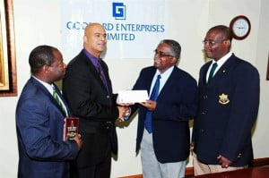 Anthony Ali (second left) presents the cheque to Captain Lubin Maxwell while Captain Alfred Taylor (left) and Warrant Officer Brian Cole (right) look on.
