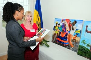 "Monique Hassell, Group Organisational Development Manager of ANSA McAL (Barbados) Ltd. and Jan Lewis, volunteer librarian at HMP Dodds browsing the prison's 2014 calendar and the submission ""Crop Over""  by Ronald Beckles. Plans are already in train for the 2015 edition."
