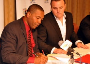 SKN Minister of Sports Glenn Phillip signs the agreement with the CPL while Damien O'Dononhue looks on