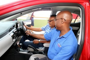 Toyota Salesman - Sinclair Roach as he shows the interior of the new model to Rodney Wilkinson.