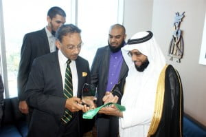 His Excellency Dr. Fahad Al Dawood (right) makes a presentation to Trade Minister Vasant Bharath (left). Looking on are Mr. Umar Kkan, TSCC Chair and Coordinator of the Delegation; and Mr. Shazaad Razul Mohammed