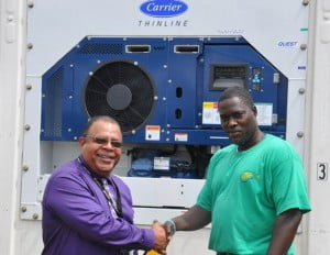 Mr. Wilbur Edwards, LIAT's Executive Manager for Cargo and Quikpak services (left) accepts the container from Mr. Casper Phillips of ERA Services