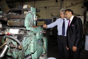 Mr. George Haloute (left) explains the mechanics of a piece of machinery to Trade Minister (right)