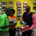 Rodney Cadogan, Senior Warehouse Assistant, Harris Paints Barbados examining his new pair of sneakers compliments Duty Free Caribbean Holdings in recognition of his reaching 1 Million Steps in 41 days as part of the NISE 100 Improvements Movement Challenge while Kim Tudor, CEO, National Initiative for Service Excellence (NISE) Inc. and Mark Anthony, Customer Service & Corporate Communications Manager, Duty Free Caribbean Holdings look on.