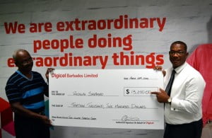 Big time winner in the 2014 Digicel Fugitive hunt, Rudolph Shepherd (left), collecting his final cheque for $13,200 from Digicel Barbados' Commercial Director, Alex Tasker.