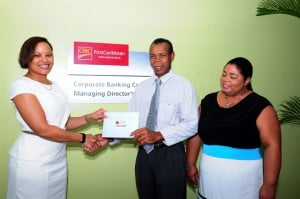 Noel Adams, president of the St. Vincent and the Grenadines Association of Barbados receives funds to go towards the continued rebuilding effort in St. Vincent and the Grenadines from Donna Wellington, Managing Director, CIBC FirstCaribbean while Maureen Adams looks on.