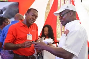 Digicel's Retail Manager, Devere Tempro, helps out this customer who visited the booth on the first day of BMEX