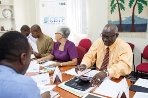 Manager of the CBTF, Anderson Lowe (right) is Chairman of the Technical Review and Selection Committee which is tasked with evaluating proposals submitted to the fund. Other members of the committee include (from left) Richard Greene, National Union of Public Workers (partly hidden); Executive Director of the TVET Council, Henderson Eastmond; and retired Human Resource Manager TMR, Claudia Smith. Backing is Paul Murphy, Ministry of Education, Science, Technology and Innovation.