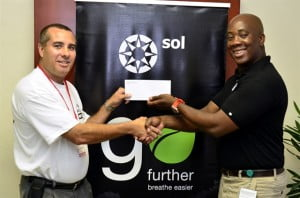 "General Manager of SOL (BARBADOS) LTD, Ezra Prescod, presenting MudDogs Chairman Courteney ""Ricky"" Holder with sponsorship in support of the June Safari Rally."