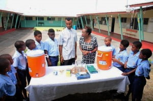 CIBC FirstCaribbean Manager, Retail Banking Channels, Paige Bryan; Ian Marshall, assistant coach and teacher; along with members of the cricket team at the Vauxhall Primary School admire the new water coolers and cups which the bank presented to the school recently.