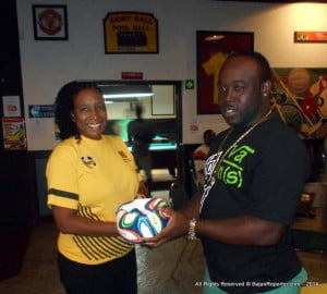 Nhamo Winn is a happy fan as he collects his official FIFA soccer ball from Global Directories Mktg Mgr Pam Roach at Lucky Horseshoe in Bagatelle!