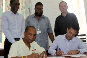 Mr Anderson Marshall, Director of Corporate Services at the Caribbean Examinations Council (left) and Mr Jaggernauth Dass, vice president, columbus business solutions – eastern caribbbean (right) signing contract while (standing from left to right) Glenroy Cumberbatch, Acting Registrar of CXC, Mr Rodney Payne, Senior Assistant Registrar - Information Systems Division, CXC and Mr Dean McIntosh, Columbus Business Solutions: Pre-Sales witness to this historical partnership.