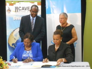 The official renaming of the UWI's CHSB is to be announced at a later date. {STANDING, L to R: Mr Dexter Moe, VP of Sagicor's Investment Mgmt Services with Dr Charmaine Gardner, Chair of th CHSB's Board of Directors. SEATED AND SIGNING: Dr's Patricia Downes-Grant with Jeannine Comma}