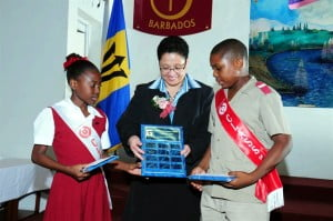 Scholarship winners Alisha Nash (left) and Renaco Griffith (right) admiring their awards with Ann Marshall, Financial Controller, West Indies Rum Distillery.