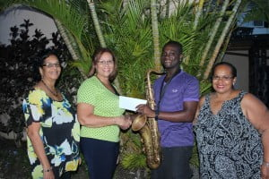 President of the Barbados Jazz Society Ann Smith (second left) presenting a cheque to saxophonist Mylon Clarke. Looking on are Treasurer Sherry Cumberbatch (left) and Secretary Cheryl Holder (right).