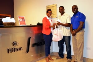 Joseph Bowen (center), accepting his Hilton Gym membership and Samsung devices from Digicel Products Manager, Fabien Barker and Hilton Recreation Manager, Julian Boyce.