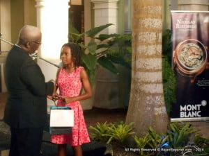Selena Grannum cracked her books and not heads, her desire to shoot ahead of her classmates paid off and she earned a Mont Blanc pen which was presented by Edu. Min. Ronald Jones at Limegrove
