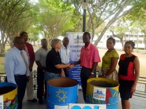 Ms. Sharon Christie presenting the cans for the City to Mr. Ulric Neblett of the Sanitation Service Authority (SSA) as SSA, TRBI and National Conservation Commission representatives look on.