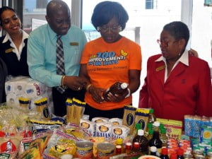 Bridgetown branch manager Steven Smith (second from left) and NISE CEO Kim Tudor (second from right) take a look through some of the food items collected for the launch of the branch's 100% Bajan food drive. Scotiabankers Vijaya Mahabir (left) and Charmaine Waterman (right) look on.
