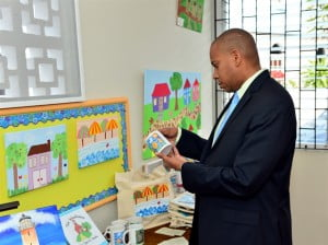 Scotiabank Managing Director Caribean East, David Noel examines some of the students artwork offered for sale to assist with the School's fundraising initiatives