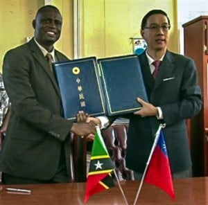 Ambassador Tsao (left) and Minister Carty after the signing of an Agricultural Technical Cooperation Agreement MOU - December 10, 2013