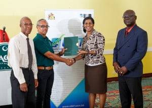 Minister of Labour, Dr Esther Byer Suckoo presents Owner of Nature Care, Russell Corrie with a proposal pack for application to the Competency-Based Training Fund while manager of the fund, Anderson Lowe (right) and Consultant, Asymetrix (which is partnering with Nature Care) Dr. Richard Graham look on.