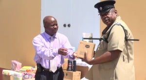 (L-R) Permanent Secretary in the Premier's Ministry Wakely Daniel hands over donation from the Dennis and Linda Thomas in Florida for the inmates of the Prison Farm to Principal Officer in Charge of the Prison Farm on Nevis Lawson Crosse on August 07, 2014