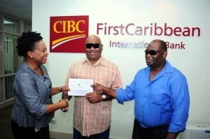 Nicole Weekes, Senior Trust Officer, Barbados Wealth & Asset Management, CIBC FirstCaribbean presents Rudyard Welch, President, and Roger Vaughan, Vice President of the National United Society for the Blind with a contribution for the society's education and sports fund.