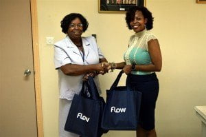 Joan Crawford, Director of the Child Care Board (Left) receiving stationary for the students from Columbus Telecommunications Barbados Limited, Corporate Communications Manager, Tracy Moore