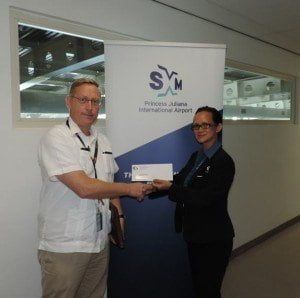 Acting manager of the Marketing and Customer Service Department of SXM, Suzy Kartokromo handing over the sponsorship check to Dr. Deketh of WIMA. (SXM Airport photo)