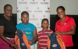 Malyssa Coles of Stansfeld Scott (RIGHT) donating to Donnah Russell of Variety (EXTREME LEFT) and two children, 2 of the 75 bags which were distributed to children across Barbados this summer in time for school.