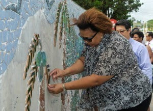 Ella Hoyos, Head of HR as she assists in the tiling of the mural.