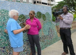 Jewel Forde and cameraman Rondell French of CBC speaking to Goldie Spieler, as they capture some of the ongoing work on the wall funded by CIBC FirstCaribbean.