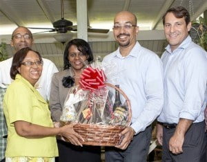 Arlene Bushell, Manager at Brown Sugar Restaurant receives a gift basket from Mount Gay staff members including from left, Andrew Straughn, Lynthia Skeete, Shawn Rudder and Managing Director, Raphael Grisoni.
