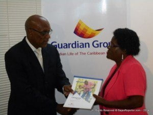 Yvonne Eugene (right) officially receives her Liberator Plus policy from Michael Austin: VP of Sales & Marketing