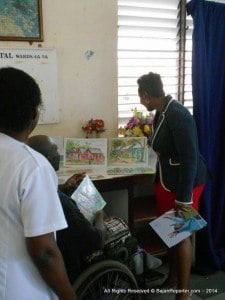 Artist Christopher Benjamin proudly talks about his piece with AVP Marketing, Sagicor Life, Mrs. Tracey Knight-Lloyd