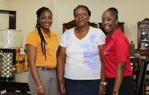 Ms. Arlene Floro (left) Marketing Manager- Unicomer Barbados Limited, and KFC Marketing Coordinator Ms. Shekelia Barrow (right) congratulate Roslind Byer, winner of October's dining room makeover package.
