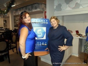Celebrating the opening of the new store, which had its soft-opening last Friday, a number of promotions are taking place, Ms. Newton (at right) said, seen here with Renee Ratcliffe (left, in blue satin) who coordinated the launch's decor.