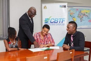 Janelle Murray, BHTA representative (second from left) signs an agreement with the Ministry of Education signaling the official start of an ambitious programme to train 300 hospitality sector managers. (From left) Shernell Marshall of the Potter Centre; Anderson Lowe, Manager of the Competency-Based Training Fund Management Unit; and Paul Murphy, Programme Director, Ministry of Education, Science, Technology and Innovation witness the moment.