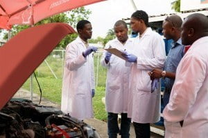"Second year students in the Automotive Engineering Programme of the Samuel Jackman Prescod Polytechnic from left, Jatione Roach, Shea Woodroffe, and Akel Bailey in consultation as Instructor Ras Babb and Adrian ""The Autodoc"" Barker look on."