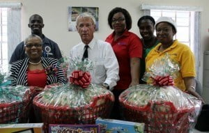 'Tis  the season of giving: From left: Deputy Director of the Child Care Board, Denise Nurse  with Chairman of C.O. Williams Construction, Sir Charles Williams, Leandra Worrell-Carrington, Kamesha Wilson and Marcelle Boxill from the Accounts Department and tractor operator Roger Holder (at back) with three of the hampers, games and shoes the company presented.