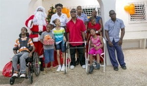 Office Administrator at Sol's operations in Barbados Carolyn Springer-Bryan smiling in the middle of the  photograph with children from the Challenor Creative Arts & Training Centre at their recent Christmas party. Santa Claus who presented the children with presents is at the left.