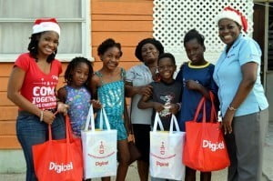 Shakida Grant (left), Digicel Marketing Executive and Donnah Russell (right) Executive Director of Variety, the Children's Charity, making donations to members of the Browne and Best families from My Lord Hill, St. Michael area.