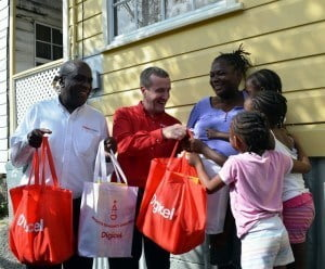 CEO of Digicel Barbados Limited, Mark Linehan (second from left) and Head or Human Resources, Kerrigan Roach (left), delivering hampers to the Harris Family.
