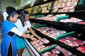Trimart employees (left to right): Rashida Gooding, Store Attendant; and Sharon Latchman, Customer Associate take a look at the pork supplied by brothers, Ronald and Dwayne Bereton who are taking part in the supermarket's Farm Fresh campaign.